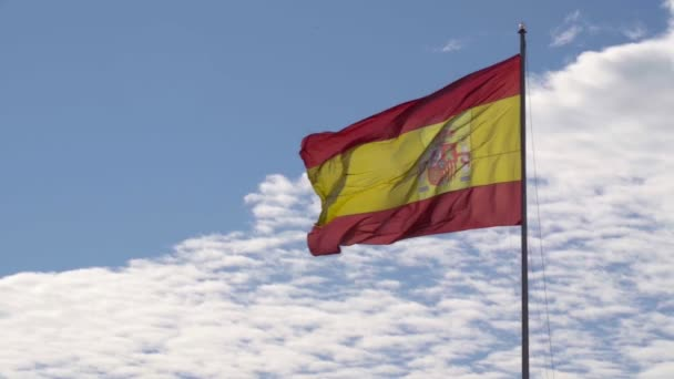 Spanish national flag against a blue and cloudy sky