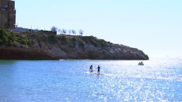 Stand up paddle board couple paddleboarding on summer vacation.