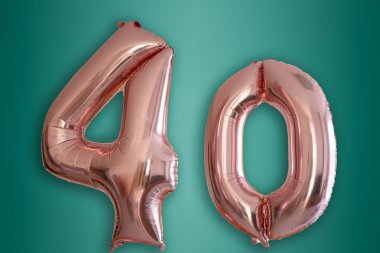 Isolated pink gold Helium Balloon in the shape of the number 40