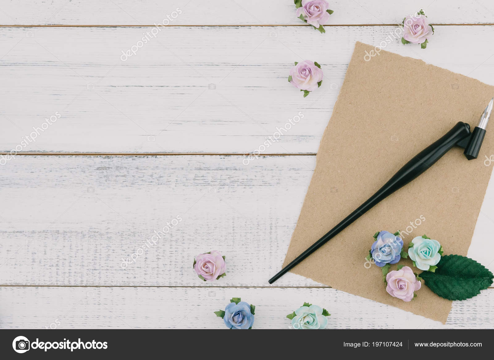 867517b488c Blank brown card and oblique pen decorate with blue tone paper flowers and green  leaves on white wood background with copy sapce– stock image