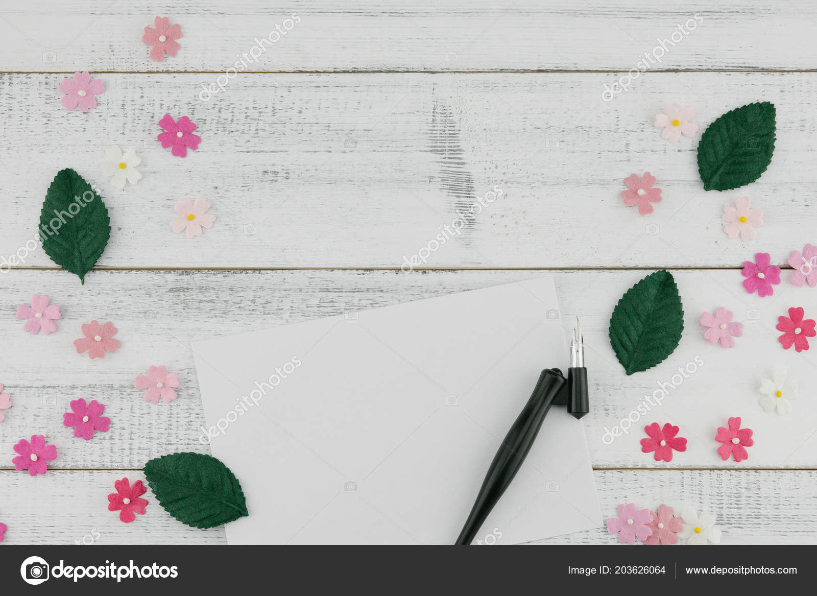 8103afb2362 Blank white card and oblique pen decorate with pink paper flowers and green  leaves on white wood background– stock image