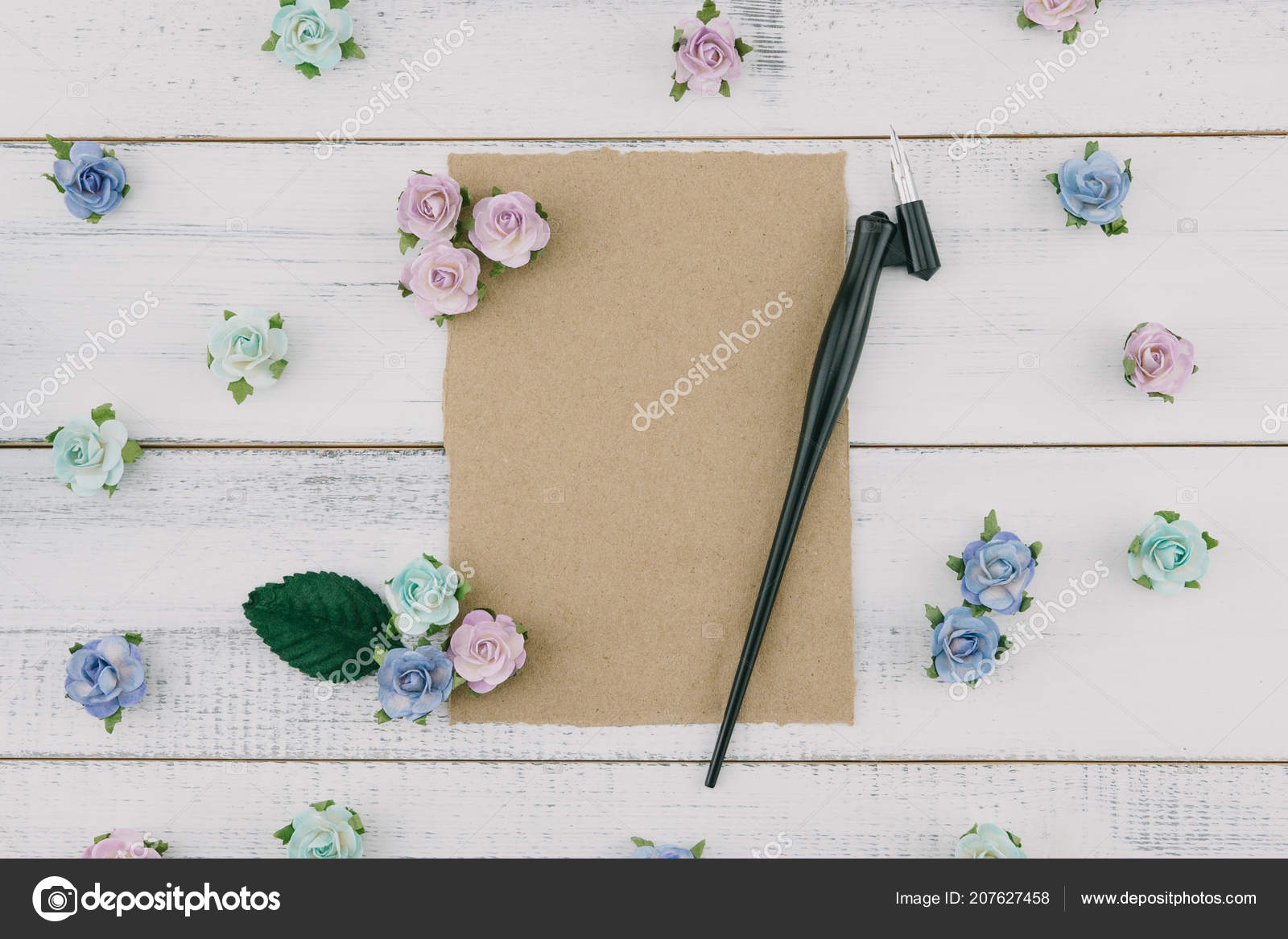 4ae730e5f3a Blank brown card and oblique pen decorate with blue tone paper flowers and green  leaves on white wood background with copy space– stock image