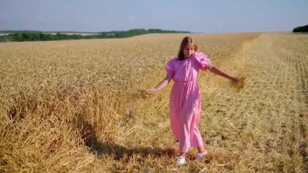 Tender teenage girl throwing wheat on field and dancing in beautiful rural place