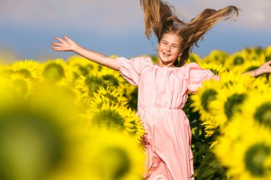 Beautiful girl bounced in a field of sunflowers rejoicing life