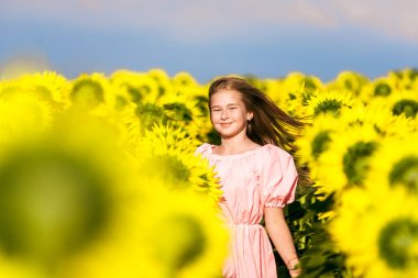 Cute girl in sunflower field posing for camera, harmony with nature, young model