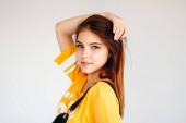 Portré gyönyörű gondtalan mosolygó tinédzser lány, sötét hosszú hajú, sárga póló, szürke háttér