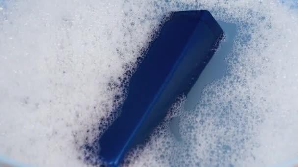 Egy kék sampondoboz úszik habos vízben. A tisztaság és a személyes gondozás fogalma.