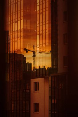 Construction of a high-rise house. Cranes reflected in the windows of a skyscraper. Concept of new buildings