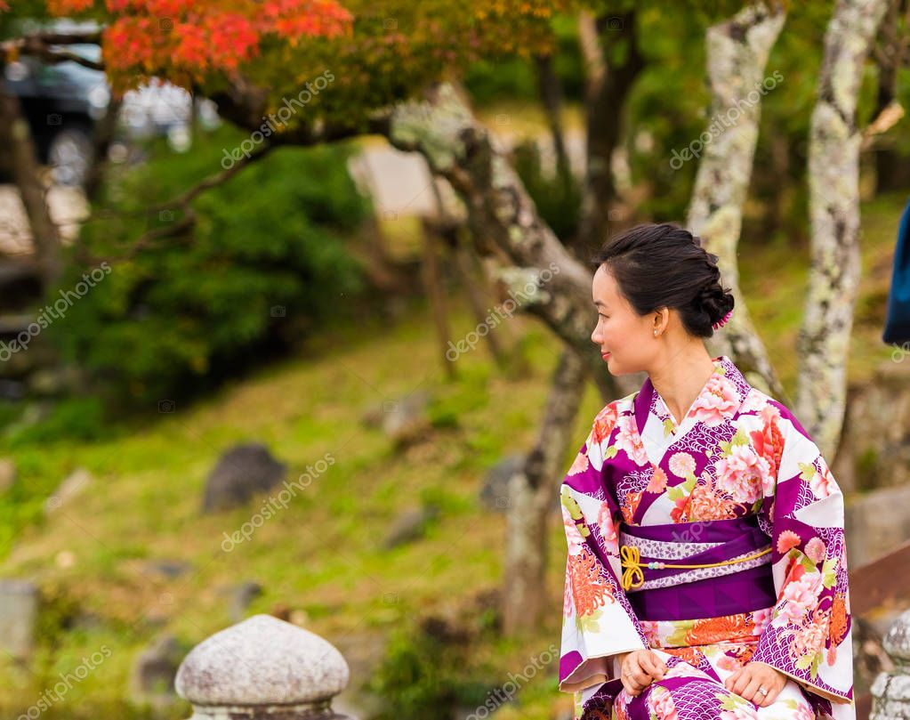 KYOTO, JAPAN - NOVEMBER 7, 2017: A girl in a kimono against the background of a city park. Copy space for text