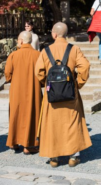 KYOTO, JAPAN - NOVEMBER 7, 2017: Monks on the territory of the temple. Vertical. Back vie