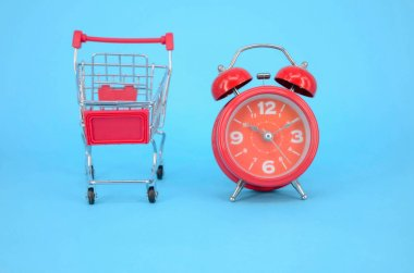 Shopping cart and classic alarm clock on blue background. Sale time market shop consumer concept. Selective focus.