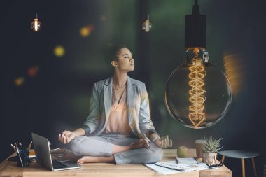 light bulb representing creative thinking and young businesswoman meditating in lotus position on work table