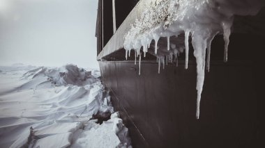 The side of a huge icebreaker of the Kara Sea stuck in the ice. Ice and icicles in a hurricane