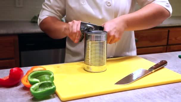 Šéfkuchař v kuchyni obklopena zeleninu používá ruku držel kovový otvírák v kontejneru červená omáčka