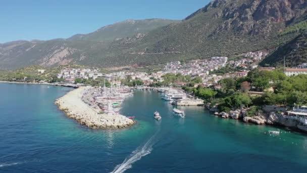 Drone, na modrém moři a v přístavu, s čluny, které jezdí dovnitř a ven do přístavu. Pohoří na pozadí Kasní Turecko