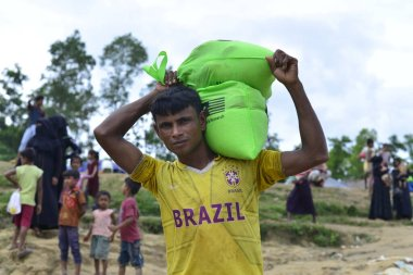 Rohingya refugees carries relief aid after collected from relief camp at Mowsuni in Teknaf, Bangladesh, on October 07, 2017. Some 582,000 Rohingya refugees have fled their homes in Myanmar and arrived in Bangladesh since late August, the United Natio