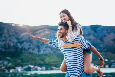 Young woman piggybacking boyfriend enjoying summer time at sea.
