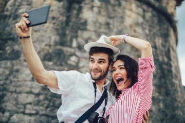 Tourist couple enjoying sightseeing and exploring city and making photo using camera