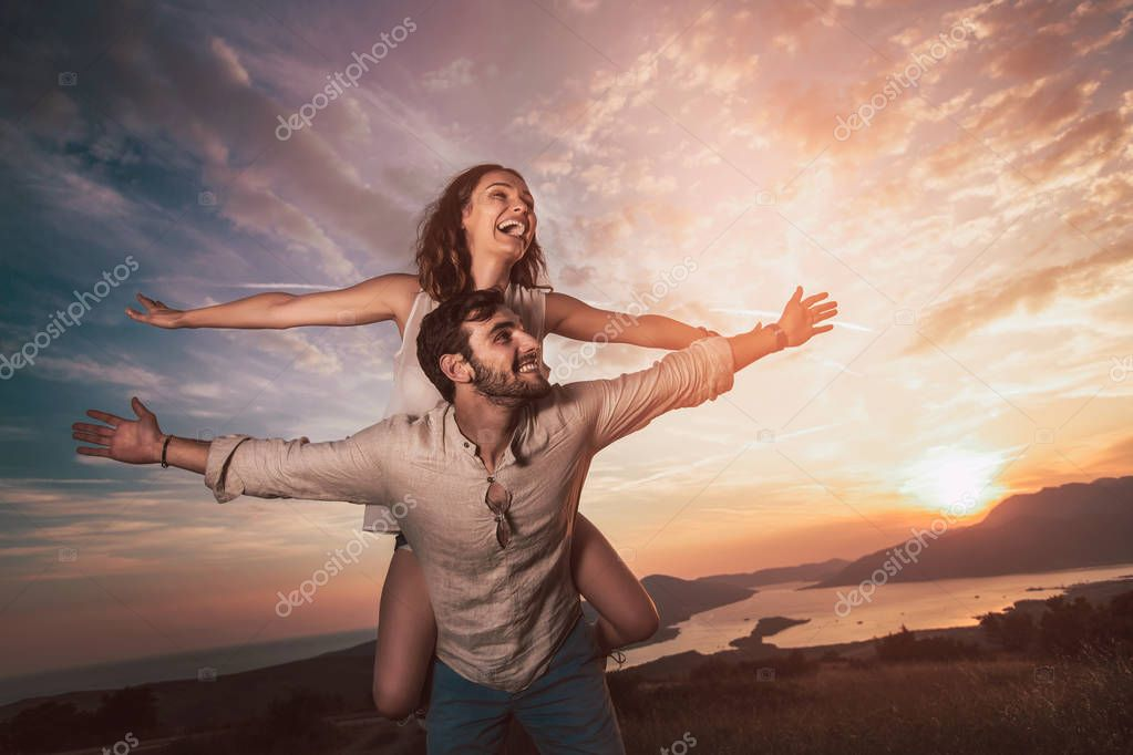 Young couple having having fun at sunset on Boka Bay
