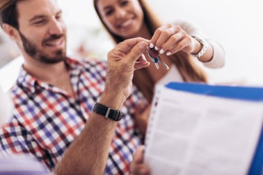 Real estate agent giving keys to couple of customers