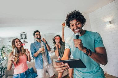 Group of friends playing karaoke at home, Concept of friendship and home entertainment