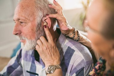 woman wearing hearing aid on male ear, close-up, hearing problem concept