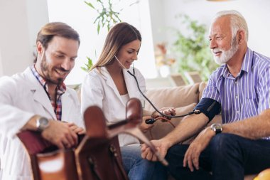 Nurse measuring blood pressure of senior man at home. Smiling to each other. Home care.