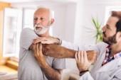 Muž s chiropraktický paže. Fyzioterapie, sportovní zranění rehabilitace. Starší muž cvičení v centru pro chiropraxe.