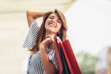 alışveriş torbaları holding ve gülümseyerek - açık havada güzel kadın