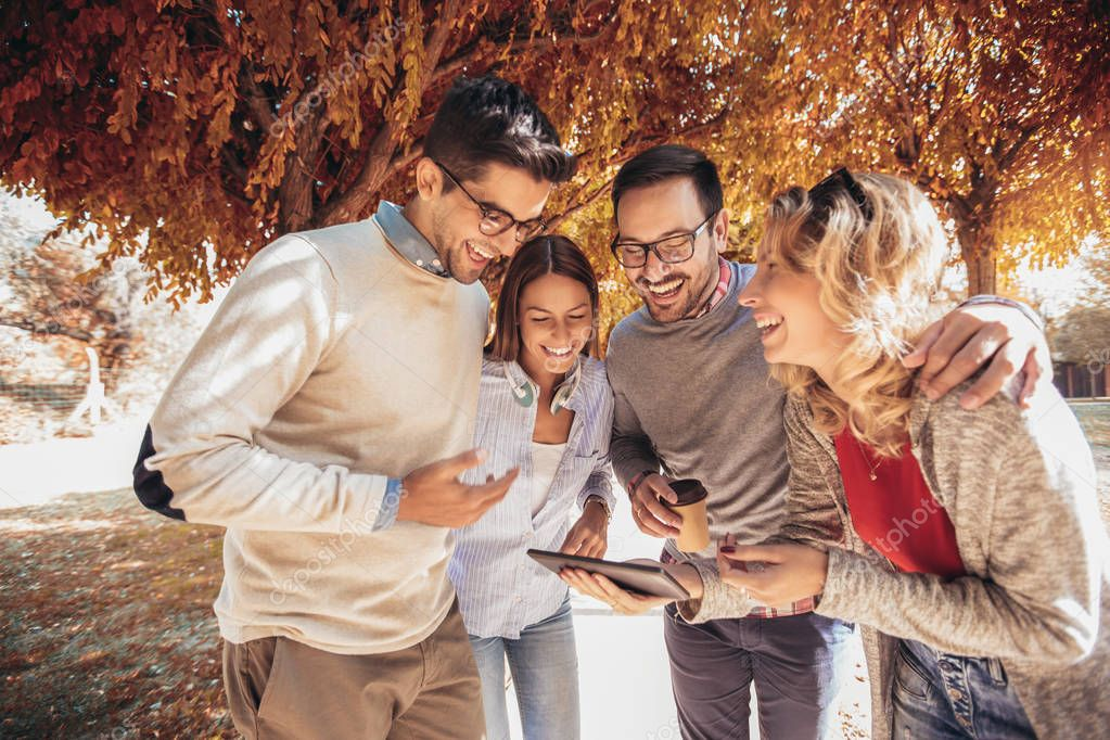Four happy smiling young friends walking outdoors in the park holding digital tablet