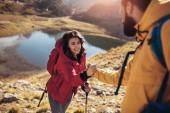 Pomocnou ruku - tramp žena získání nápovědy na výlet šťastné překonání překážky