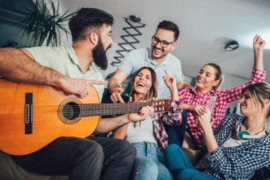 Group of happy young friends with guitar having fun and drinking beer in home interior