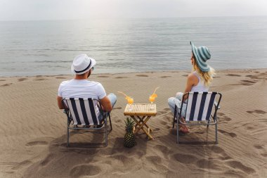Couple on a deck chair relaxing on the beach. Happy couple enjoy on the beach during summer vacations