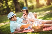 Beautiful couple enjoying picnic time outdoor reading book