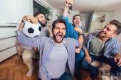 Sledování sportu v televizi společně doma muži křičí veselé. Skupina přátel, sedí na gauči a sleduje fotbal.