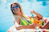 Nyári vakáció. Élvezi a barnító nő a bikini, a medence felfújható matrac.