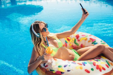 Summer Vacation. Enjoying suntan Woman in bikini on the inflatable mattress in the swimming pool using digital tablet