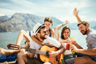 Group of friends with guitar having fun on the beach.