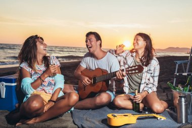 Group of friends with guitar having fun on the beach at sunset.
