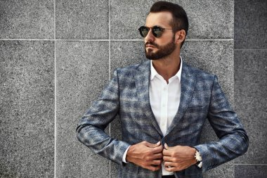 Portrait of sexy handsome fashion businessman model dressed in elegant checkered suit posing near gray wall on street background. Metrosexual