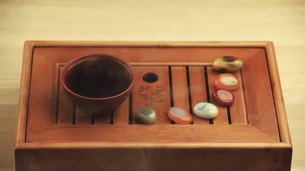 Čínský čaj horký pohár bambus stůl sandál vonných tyčinek kameny hd záběry