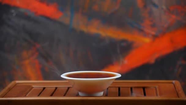 Čínské černé horký čaj pohár bambusový stůl hd záběry