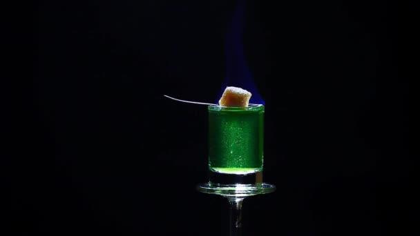 Absinth Schuss Glas Rohrzuckerlöffel Feuer dunklen Hintergrund hd Filmmaterial