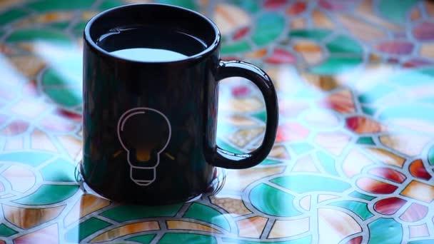Black tea mug bulb symbol water table hd footage