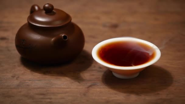 Teapot black hot tea cup wooden desk hd footage