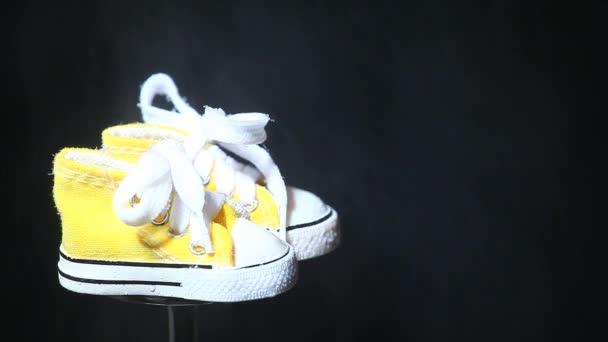 kapky vody žluté malé boty tmavé pozadí, nikdo hd záběry