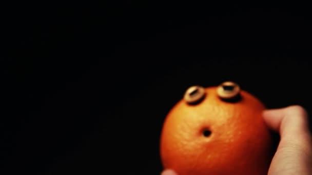 orange plastic blue eyes dark background hand hd footage