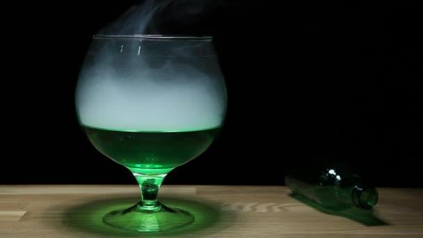 Absinthe Glas Rauch leere grüne Flasche Holztisch hd Filmmaterial niemand