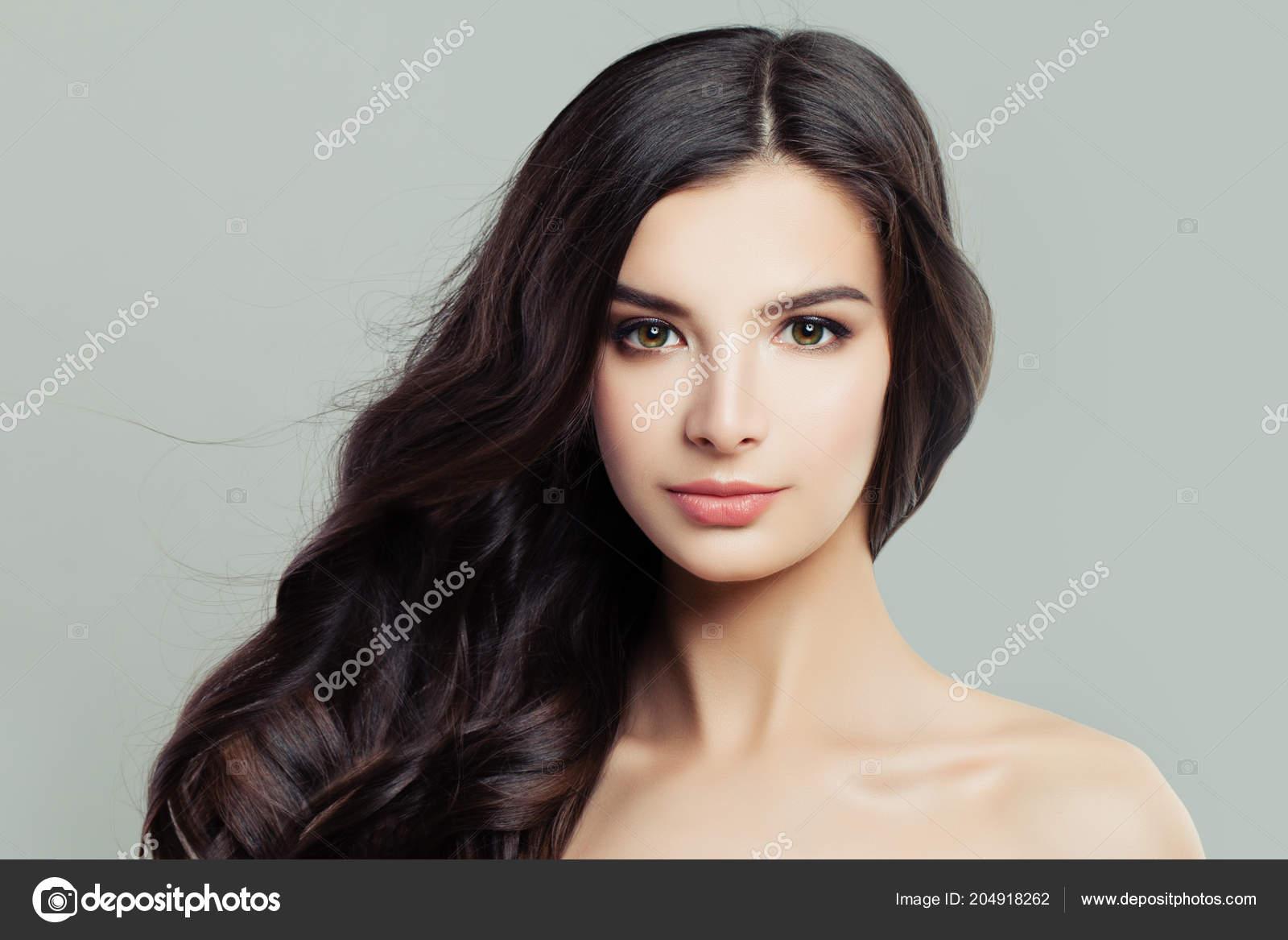 Hermosa mujer joven con peinado largo marrón y piel clara. Tratamiento  facial 4f5bb97b1d39