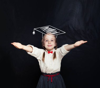 Child in graduation hat in classroom against chalkboard. School concep